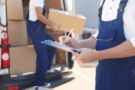 Delivery man checking list on clipboard near car