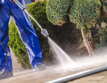 Men Washing Garden Residential Brick Paths With Professional Pressure Washer